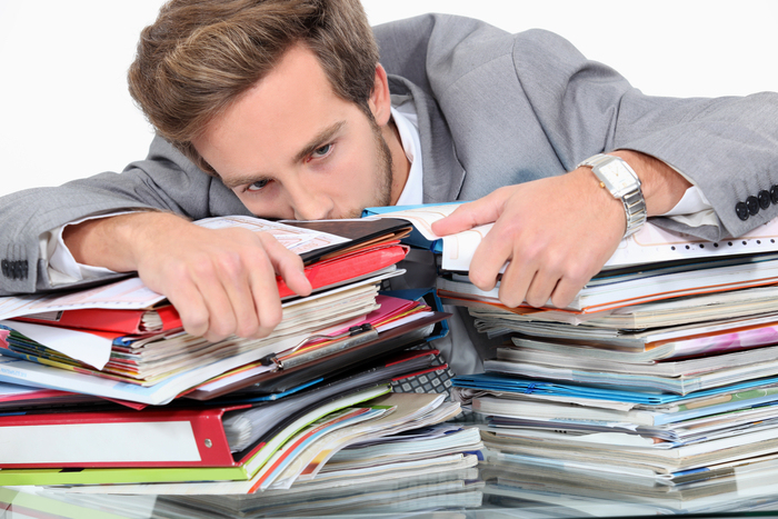 Man drowning in stacks of paperwork